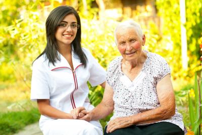 nurse visiting an elderly women holding her hands
