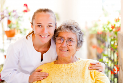 female nurse and elderly woman smiling
