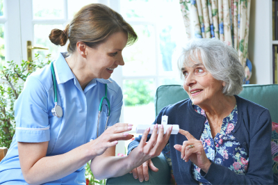 Nurse advising senior woman on taking medication at home
