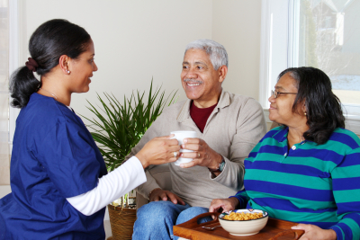 caregiver and two elder couple smiling