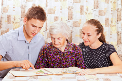 young man and girl teaching elderly woman