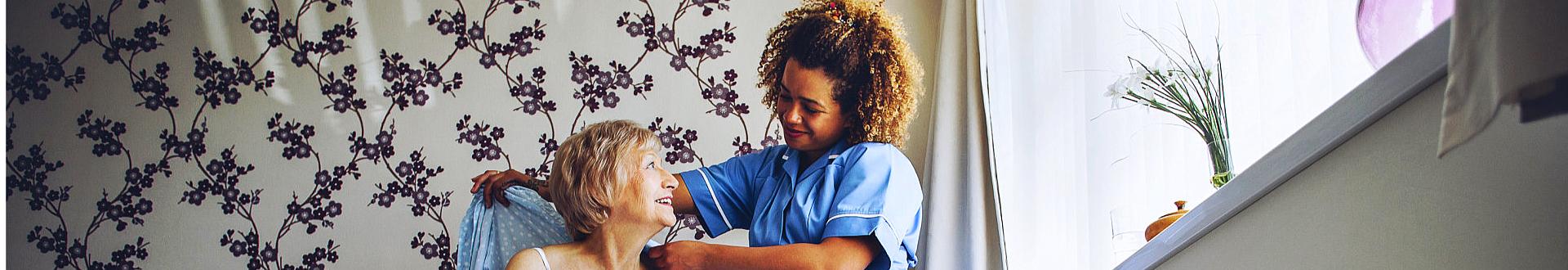 caregiver helping senior woman in dressing